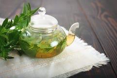 Tetera con el primer del té de la menta en la tabla Fotografía de archivo libre de regalías