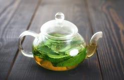 Tetera con el primer del té de la menta en la tabla Fotos de archivo