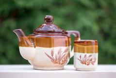 Tetera con la taza de té exteriormente Fotografía de archivo libre de regalías