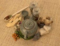 Tetera con las hierbas y las raíces Foto de archivo libre de regalías