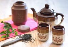 Tetera con las tazas de té y los leavs del té Imagenes de archivo