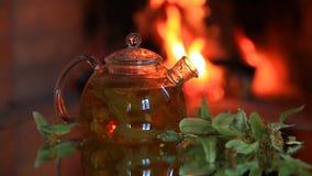 Tetera con té de la cal cerca de la chimenea almacen de video