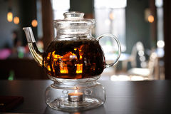 Tetera de cristal con el té calentado con la vela Fotos de archivo