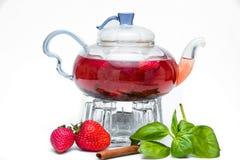 Tetera de cristal con té de la baya imagen de archivo libre de regalías