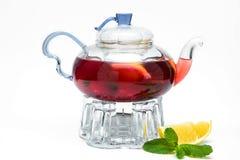 Tetera de cristal con té de la baya imagen de archivo