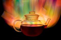 Tetera de cristal con té rojo y fuego que mira el fondo foto de archivo libre de regalías
