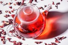 Tetera de cristal transparente con té del hibisco y té dispersado Fotos de archivo
