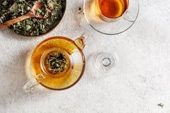 Tetera de cristal y una taza de té con infusión de hierbas imagen de archivo