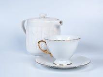 Tetera de Infuser con la taza de té en el fondo blanco Imagen de archivo libre de regalías