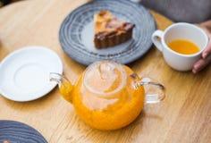Tetera de té anaranjado y un pice de la torta fotografía de archivo
