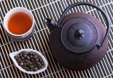 Tetera del arrabio con la taza de té y las hojas de té Foto de archivo libre de regalías