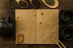 Tetera negra, dos tazas, una colección de té, manzanas secadas, libro abierto del viejo espacio en blanco en fondo de madera Fotografía de archivo libre de regalías