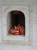 Tetera roja del juego de té de la porcelana en la ventana de la ciudad histórica hous Imagen de archivo