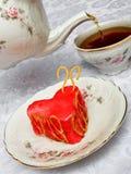 Tetera, taza de té y torta en forma de un corazón Imagen de archivo