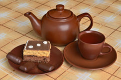 Tetera, una taza de té, tortas y dulces Imagenes de archivo