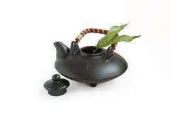 Tetera y hojas de té orientales negras Imagen de archivo