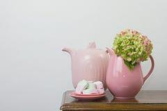 Tetera y melcochas rosadas Imágenes de archivo libres de regalías