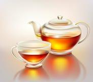 Tetera y taza de cristal con té Foto de archivo libre de regalías