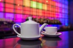 Tetera y taza de té blancas en fondo de las luces del color Fotos de archivo