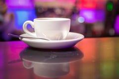 Tetera y taza de té blancas en fondo de las luces del color Imagenes de archivo