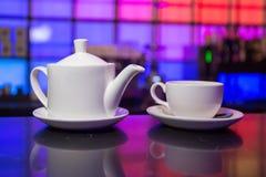 Tetera y taza de té blancas en fondo de las luces del color Foto de archivo libre de regalías