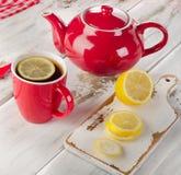 Tetera y tazas con las rebanadas del limón en la tabla de madera Foto de archivo libre de regalías