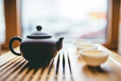 Tetera y tazas con té chino en la tabla para la ceremonia de té imagen de archivo