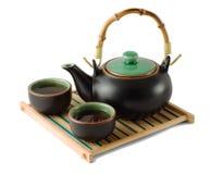 Tetera y tazas de té de Brown en el trivet de madera Fotos de archivo