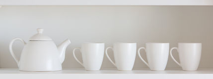 Tetera y tazas en el estante Imagen de archivo