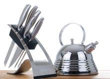 Tetera y un conjunto de knifes en un fondo blanco Imagen de archivo libre de regalías