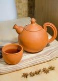 Tetera y una taza de té caliente Foto de archivo libre de regalías