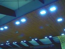 Teto luminoso de telhas quadradas Teto de madeira com painéis da iluminação imagem de stock