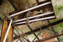 Teto Rotted e dispositivo elétrico claro fluorescente danificado na construção abandonada fotografia de stock