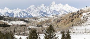 Teton bergskedja bak skogar, utlöpare och fält arkivfoto