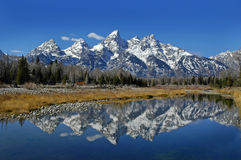 Teton Mountain Range. Reflecting in river water with surrounding rocks and plants Royalty Free Stock Photos