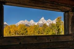 Tetons em Autumn Through uma janela de cabine Fotografia de Stock Royalty Free