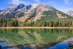 Tetons s'est reflété dans le lac string un jour ensoleillé d'automne images libres de droits