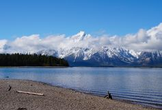 The Tetons After the Storm. Snow covers the Tetons after an Autumn storm complimenting the beautiful blue of the lake and sky stock photography