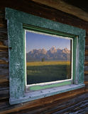 Tetons&Window. The Teton Mountain Range reflecting in the window of a ranch house, located in Grand Teton National Park, Wyoming Royalty Free Stock Images