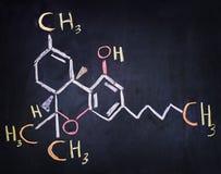 Tetrahydro-cannabinol & x28; THC& x29; formel som är skriftlig på ett svart bräde Fotografering för Bildbyråer
