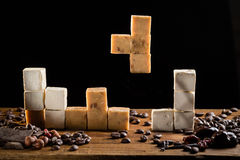 Tetris with caramel candies and sweet turkish delights. Caramel candies and sweet turkish delights squares are formed like tetris pieces. Concept of game with stock photos