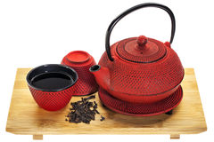 Tetsubin and oolong tea. Red hobnail tetsubin (traditional cast iron Japenese teapot) with a cup of oolong tea on a bamboo tray Stock Photos
