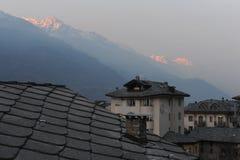 Tetti della città del San Vincenzo in d'Aosta della valle d'Aosta Valle in Italia con le alpi italiane nell'inverno al crepusco Immagine Stock