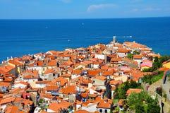 Tetti della città Piran con un mare blu luminoso nei precedenti Fotografie Stock Libere da Diritti