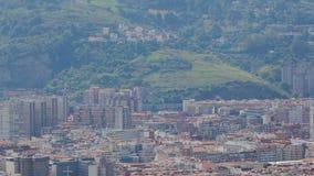 Tetti densi della città al piede della collina verde, della vita urbana e della natura, pentola verticale archivi video