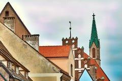 Tetti rossi di vecchie case in via di iela di Skarnu con la chiesa di St Johns nei precedenti Riga, Lettonia Fotografie Stock Libere da Diritti