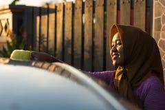 Tetto alto vicino dell'automobile di lavaggio della donna del hijab del colpo con un sorriso immagini stock libere da diritti