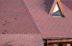 Tetto Asphalt Shingles e finestra della mansarda della soffitta Costruzione del tetto Riparazione di tetto Grondaia della pioggia fotografia stock