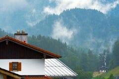 Tetto del cottage contro la foresta e le nuvole alpine Fotografie Stock