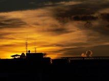 Tetto della siluetta nel cielo di sera Immagine Stock